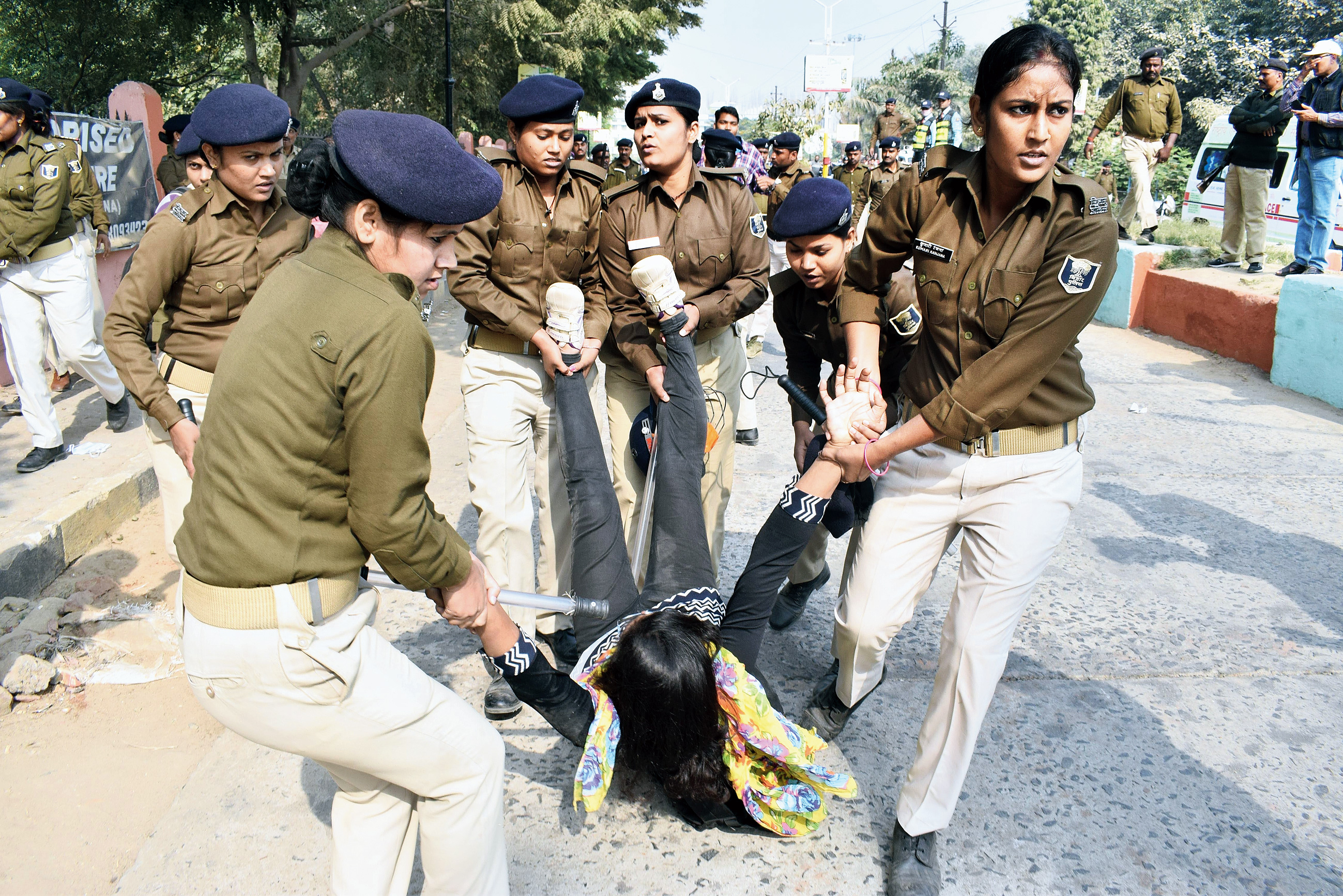 Policewomen lift away a nursing student during the protest on the IGIMS campus on Tuesday.