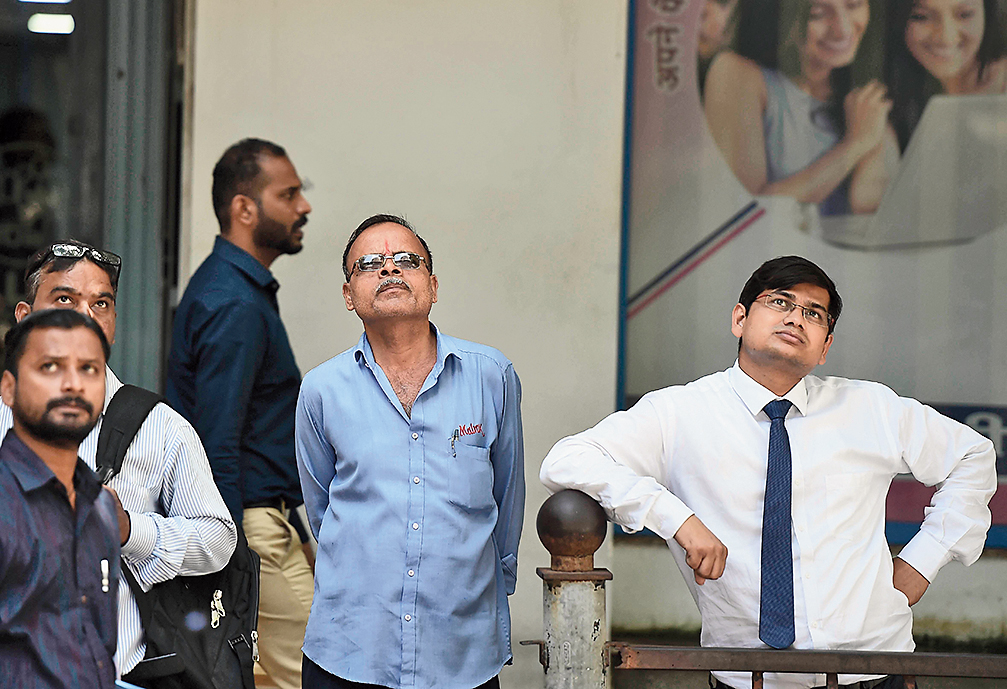 People watch the stock slide on a digital screen in Mumbai on Friday.