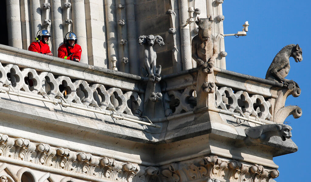 Fire fighters wait at a balcony of Notre Dame cathedral Wednesday, April 17, 2019 in Paris.