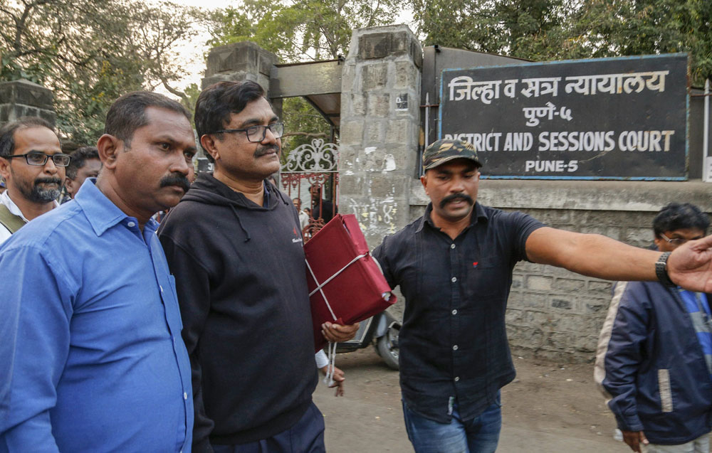Activist Anand Teltumbde (black pullover) leaves after Pune District and Sessions Court released him in Bhima Koregaon case, in Pune on February 2, 2019.