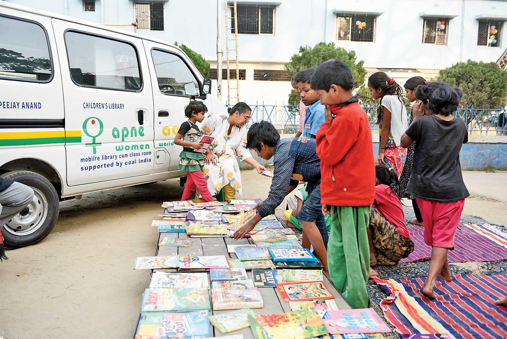 Children browse books brought by the mobile library in Sonagachhi on Monday.