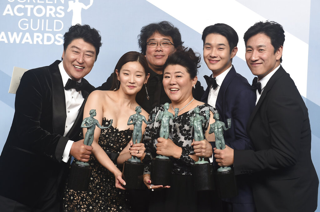 Kang-Ho Song, from left, Park So-dam, Bong Joon-ho, Jang Hye-jin, Choi Woo-shik, and Lee Sun Gyun pose in the press room with the award for outstanding performance by a cast in a motion picture for