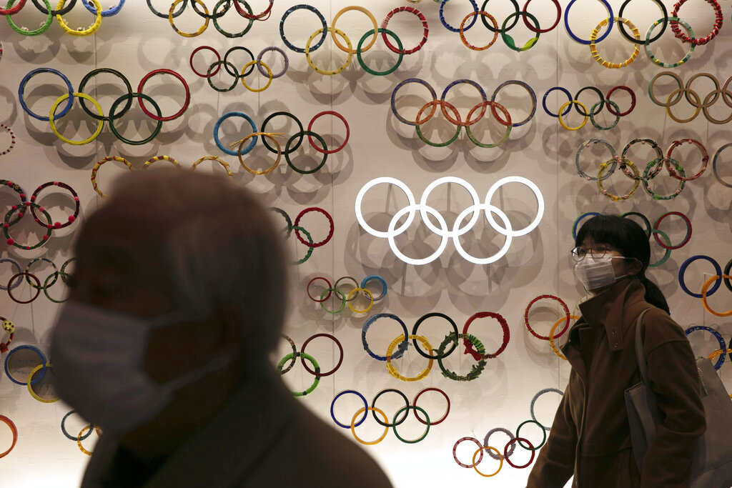 Two people wear masks as they visit the newly opened Japan Olympic Museum located near the New National Stadium on Sunday