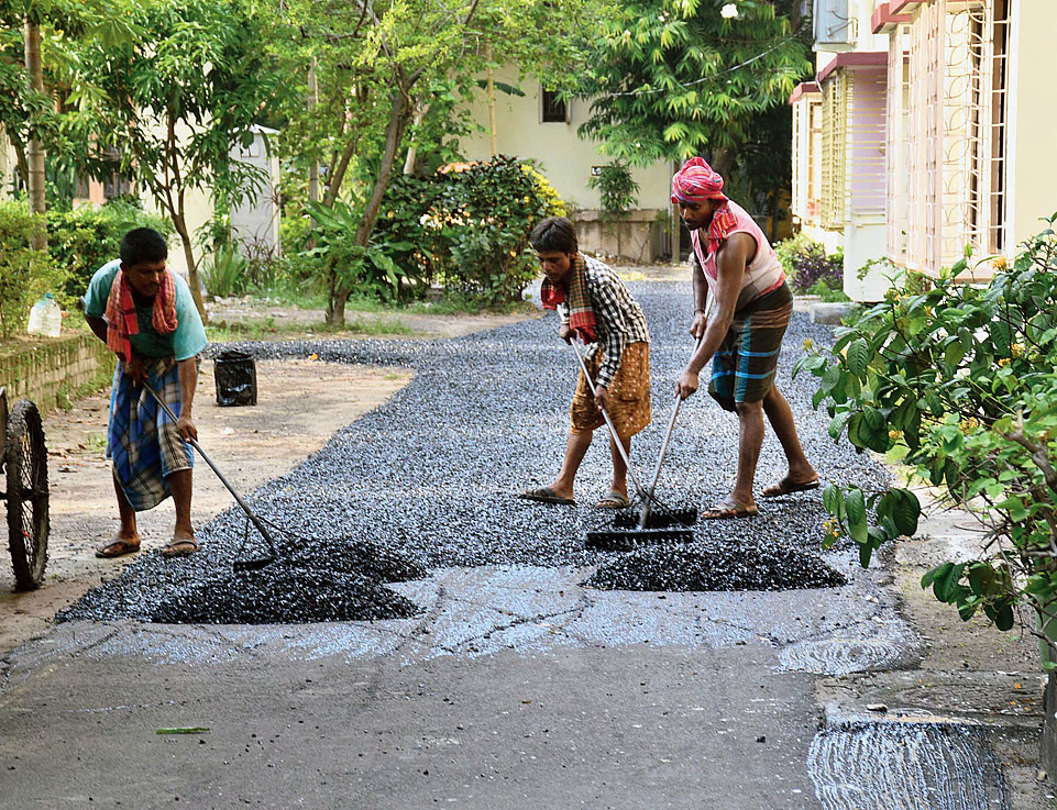 Workers lay stone chips on a layer of fresh bitumen in Purbachal