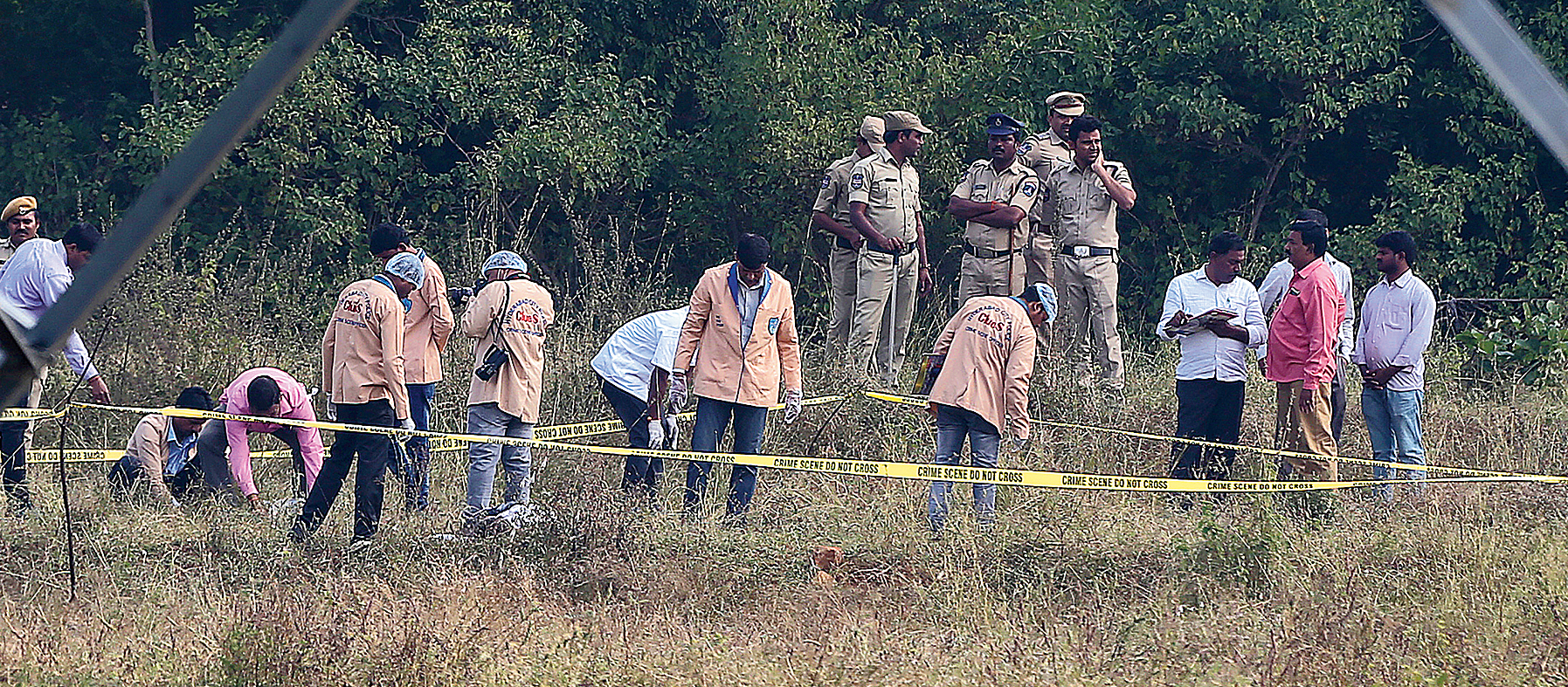 Policemen watch forensic experts investigate the site where the four rape-and-murder suspects were killed in Shadnagar near Hyderabad on Friday.