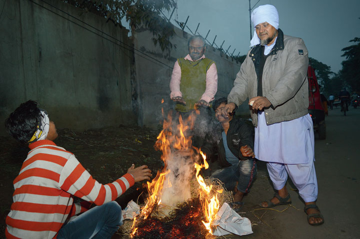 People light a bonfire to keep themselves warm in Sakchi, Jamshedpur, on Thursday