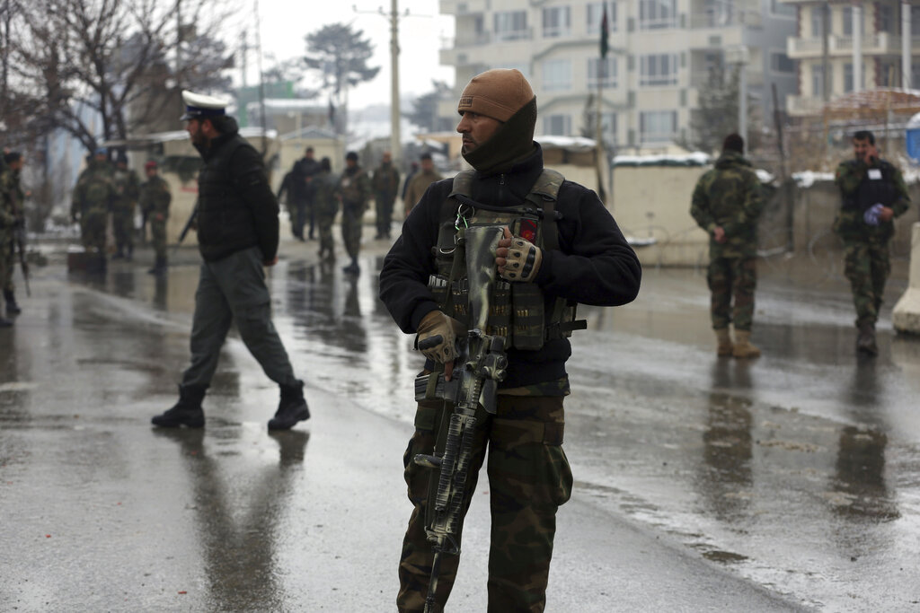 In this Feb. 11, 2020, photo, national army soldiers stand guard at the site of suicide attack near the military academy in Kabul, Afghanistan, A United Nations report says Afghanistan passed a grim milestone with more than 100,000 civilians killed or hurt in the last 10 years.