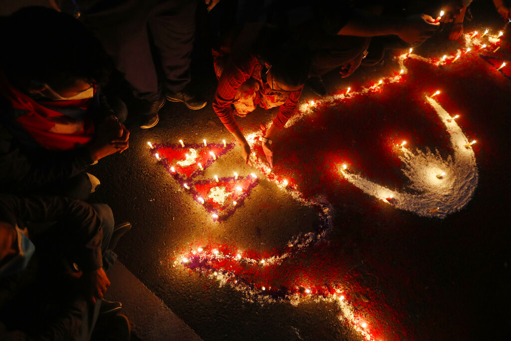 People light candles on an outline of the new map of Nepal drawn on a road as they celebrate the approval of the political map to include territory claimed by both India and Nepal, in Kathmandu, Nepal, Saturday, June 13, 2020.