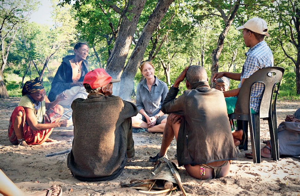 Geneticist Vanessa Hayes learning how to make a fire with Jul'hoansi hunters in the now-dried homeland of the greater Kalahari of Namibia.