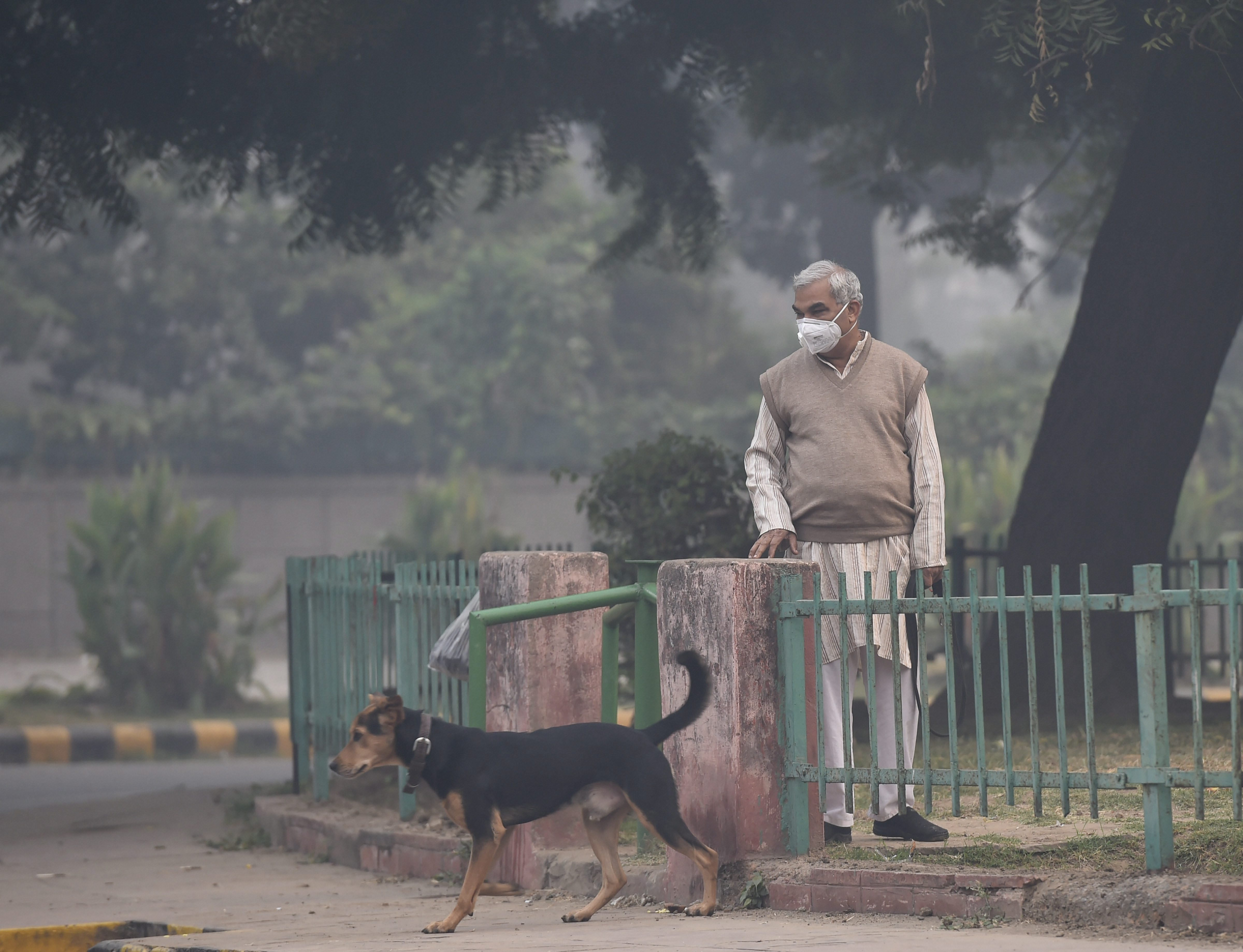 Morning walkers wear pollution masks as a thick haze engulfs Delhi a day after Diwali on Thursday.