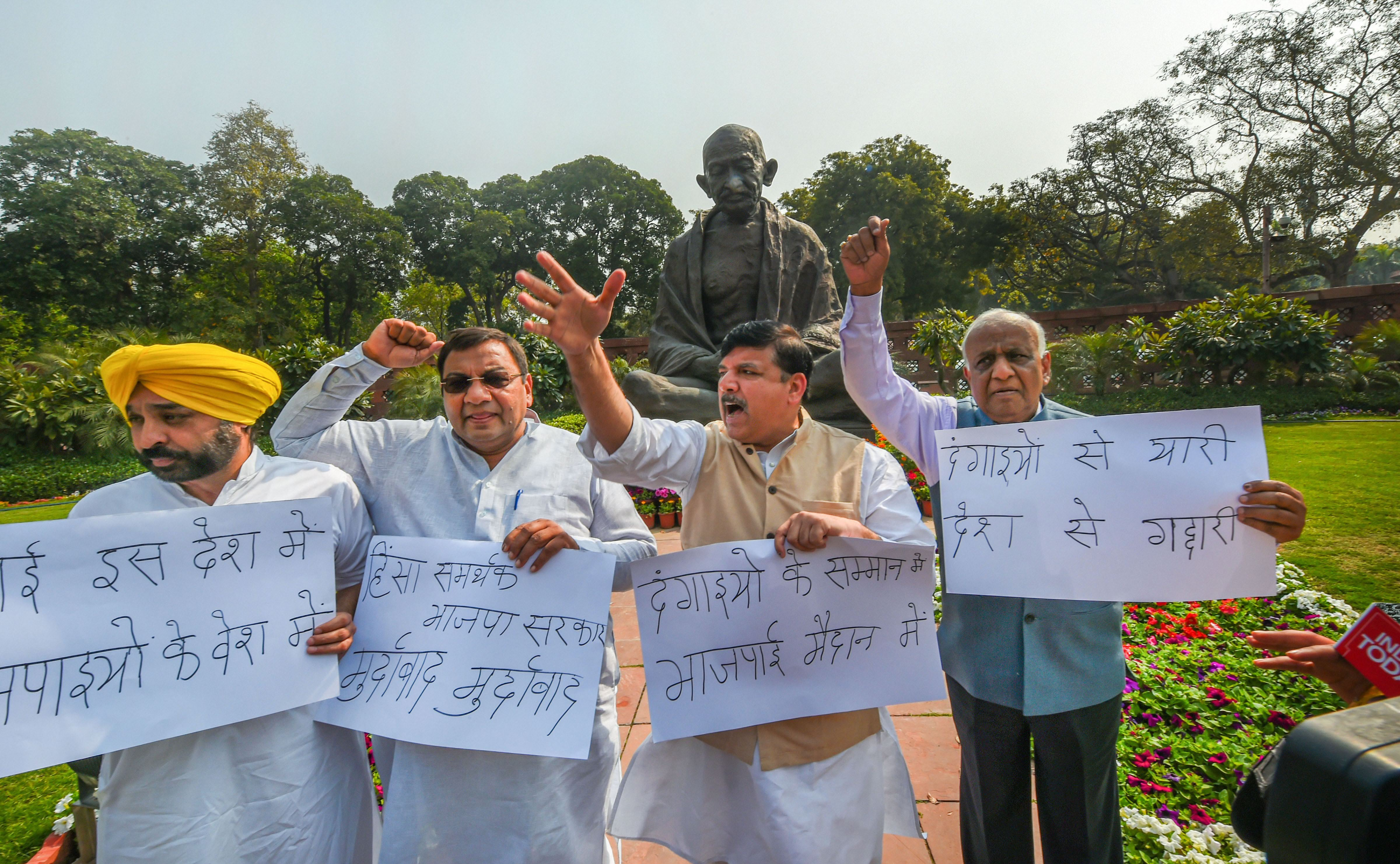Aam Aadmi Party MPs Sanjay Singh, Bhagwant Mann, N. D. Gupta and Sushil Gupta raise slogans during a protest over Delhi violence, at Parliament during the ongoing Budget Session, in New Delhi, Monday, March 2, 2020