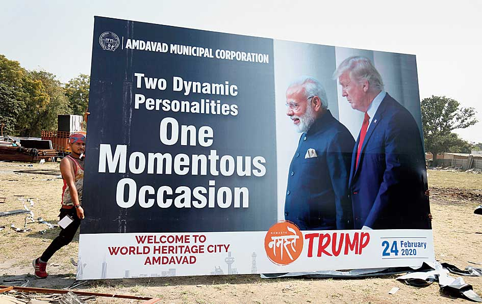 Workers carry a hoarding on Donald Trump's upcoming visit in Ahmedabad on Wednesday.