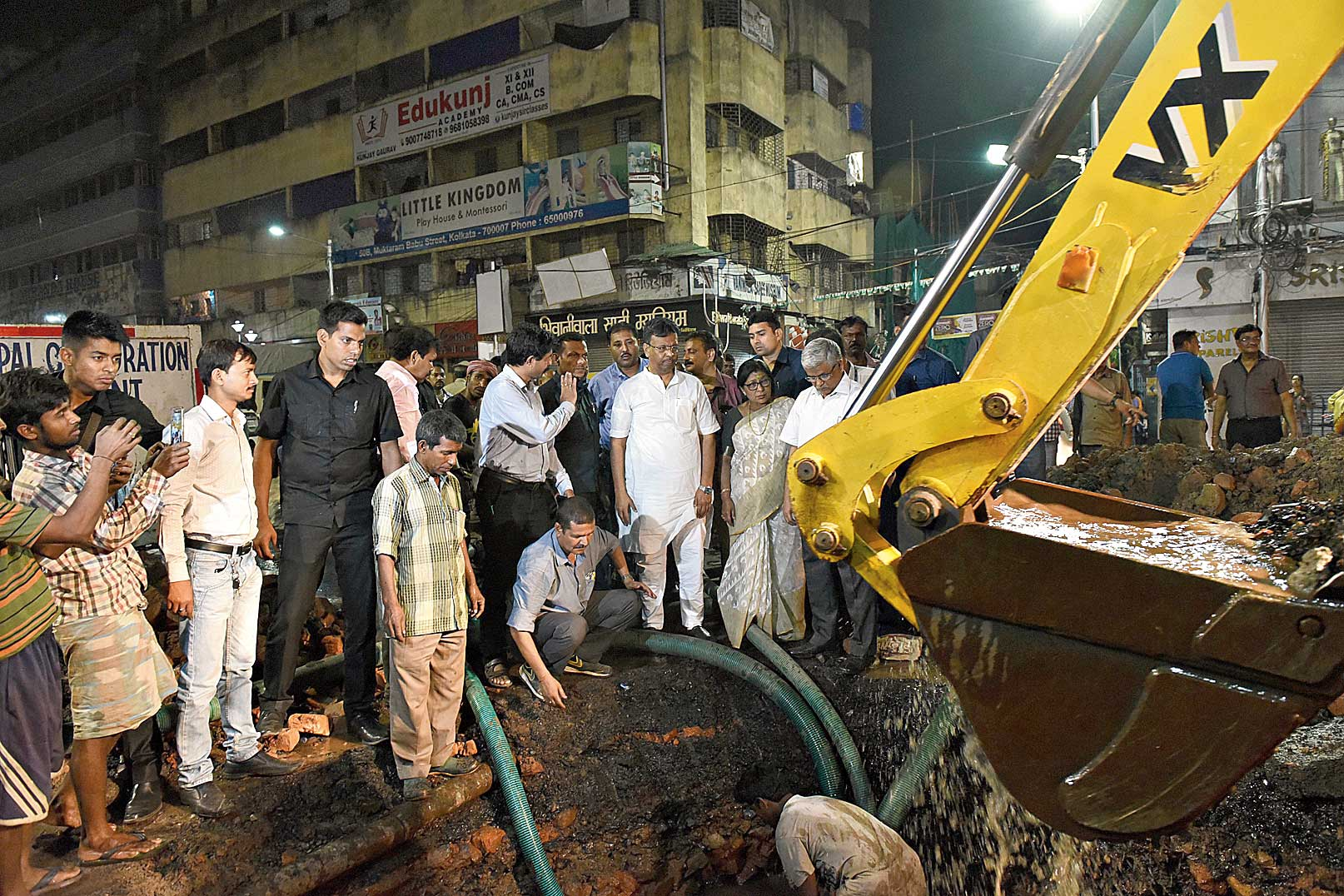 Mayor Firhad Hakim on CR Avenue in front of Ram Mandir, where an underground water pipe has sprung a leak, on Monday evening. A payloader cuts a trench on the Esplanade-bound flank of the road to let civic workers access the pipe.