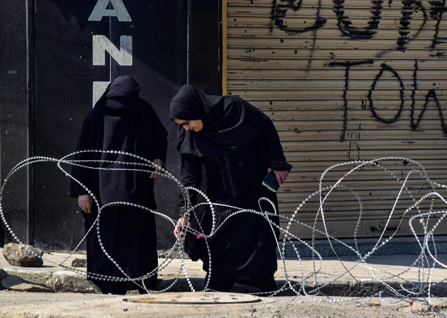 Women walk through a blocked road in downtown Srinagar on Sunday. Restrictions were imposed in the city after a strike called by trade bodies against the NIA summons to moderate Hurriyat Conference chairman Mirwaiz Umar Farooq.
