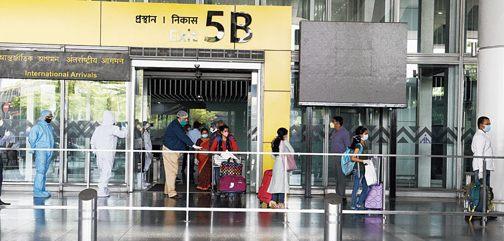 Passengers who arrived from Dhaka on an Air India flight come out of the city airport on Monday afternoon.
