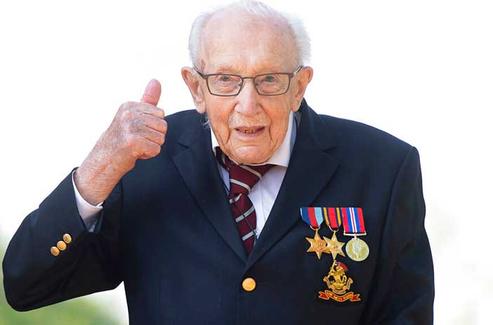 In this April 16, 2020, file photo, Captain Tom Moore gestures at his home in Marston Moretaine, Bedfordshire, England.