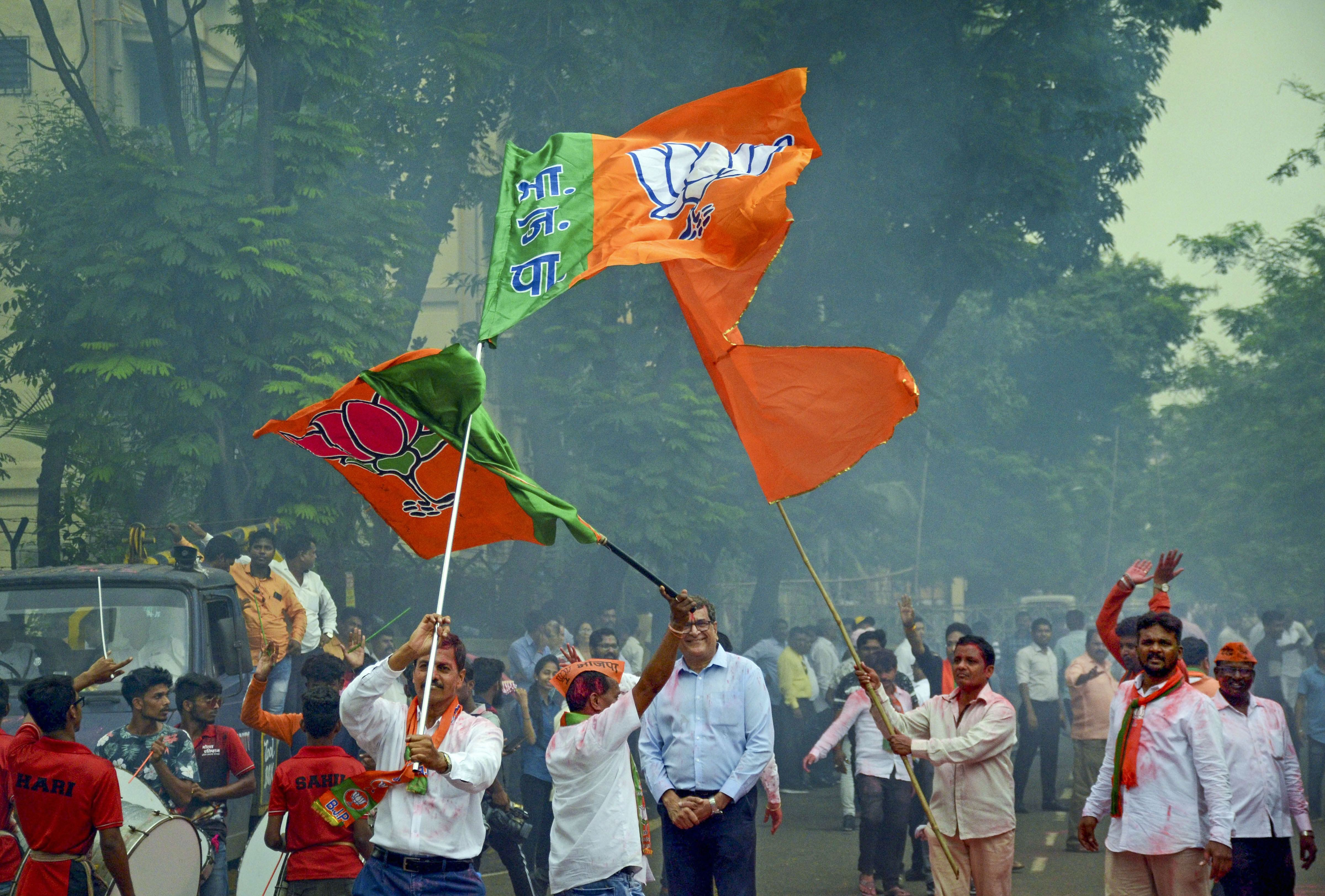 BJP and Shiv Sena workers celebrate their victory in the Maharashtra Assembly elections in Navi Mumbai on October 24.