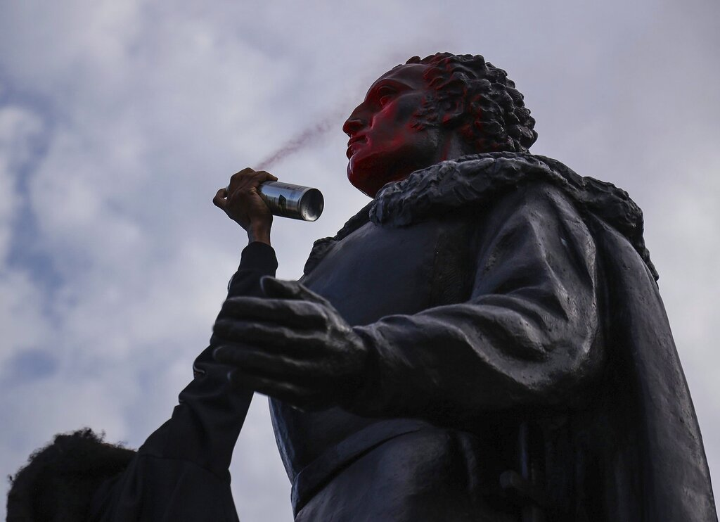 A protester spray paints the face of the statue of Christopher Columbus as the small group of protesters walked through Bayside in Miami and defaced bronze statue of Columbus and Ponce de Leon on Wednesday, June 10, 2020