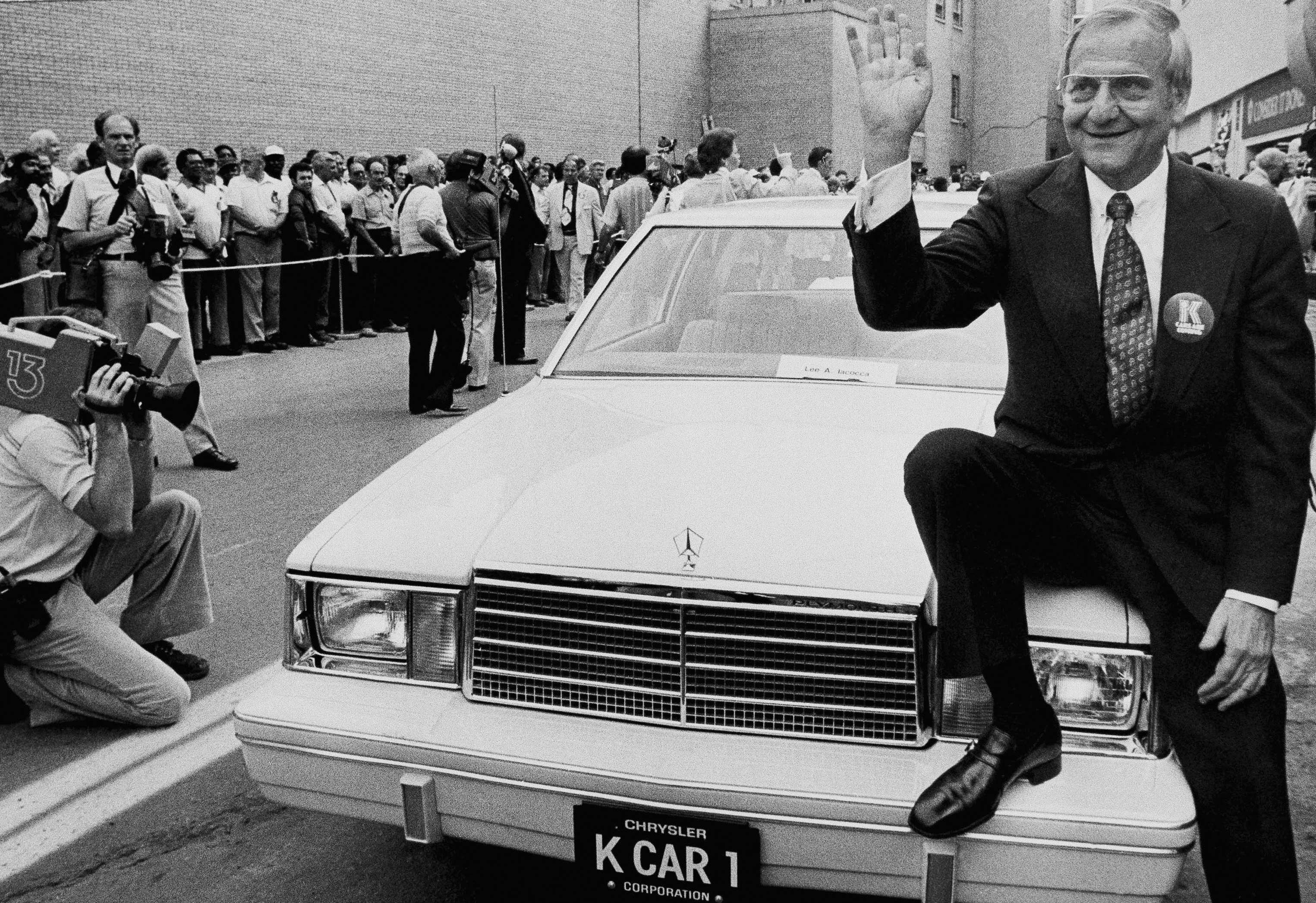 In this August 6, 1980, file photo, Chrysler Corp. chairman Lee Iacocca sits on the hood of K Car Number One, a Plymouth Reliant, in Detroit.