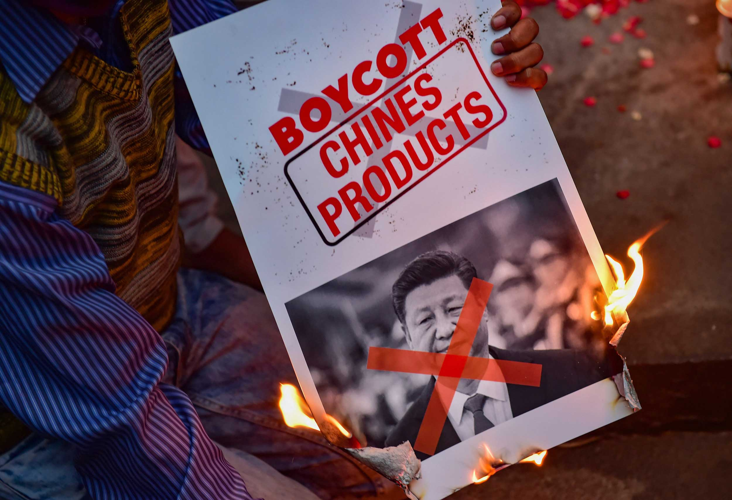 A man burns a poster of Chinese President Xi Jinping in Bangalore on Wednesday.