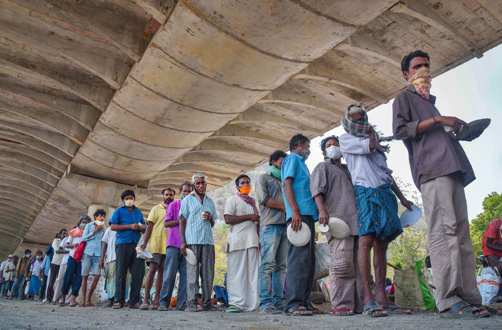 Stranded migrant labourers stand in a queue to receive food from volunteers as they take shelter under a flyover after leaving a quarantine facility, during the fourth phase of Covid-19 lockdown, in Vijayawada, Sunday, May 24, 2020.