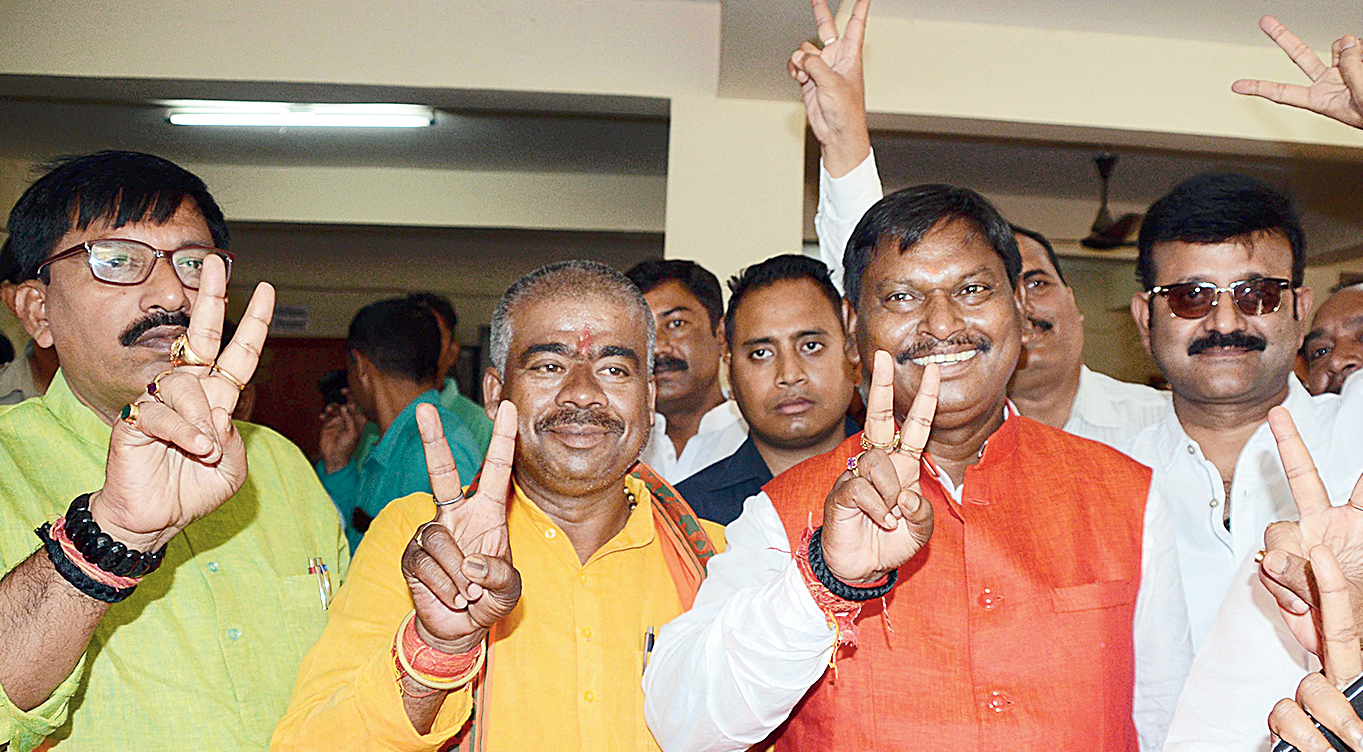 Arjun Munda (in red jacket) flashes the victory sign at state BJP headquarters in Ranchi on Friday.