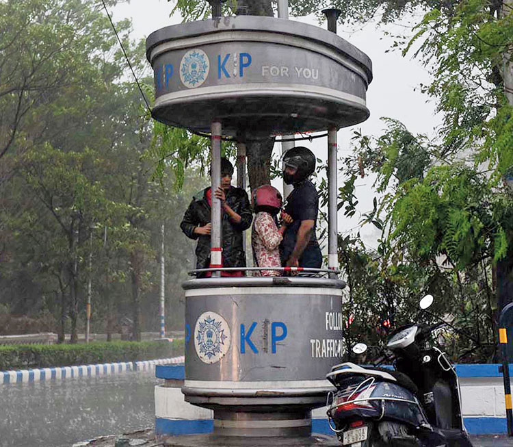 Commuters take shelter from the rain in a police booth near Victoria Memorial on Wednesday.