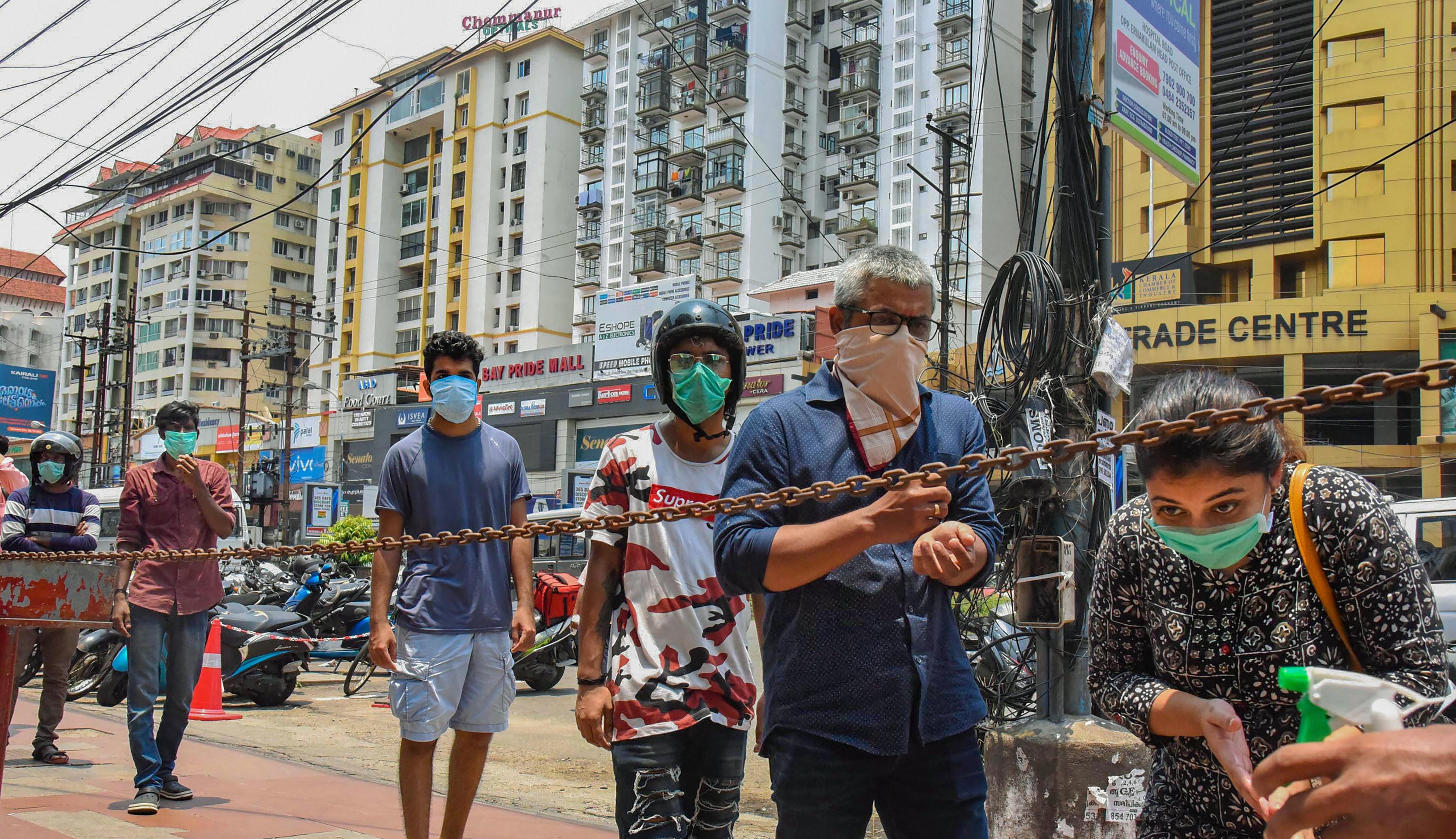People stand in a queue at a mobile phone shopping complex to purchase and repair mobile phones during the nationwide lockdown in the wake of coronavirus pandemic, in Kochi, Sunday, April 19, 2020.