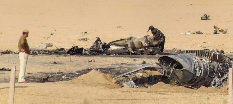 Policemen and officials stand near the remains of the MiG-21 Bison fighter jet after it crashed near Bikaner on Friday.