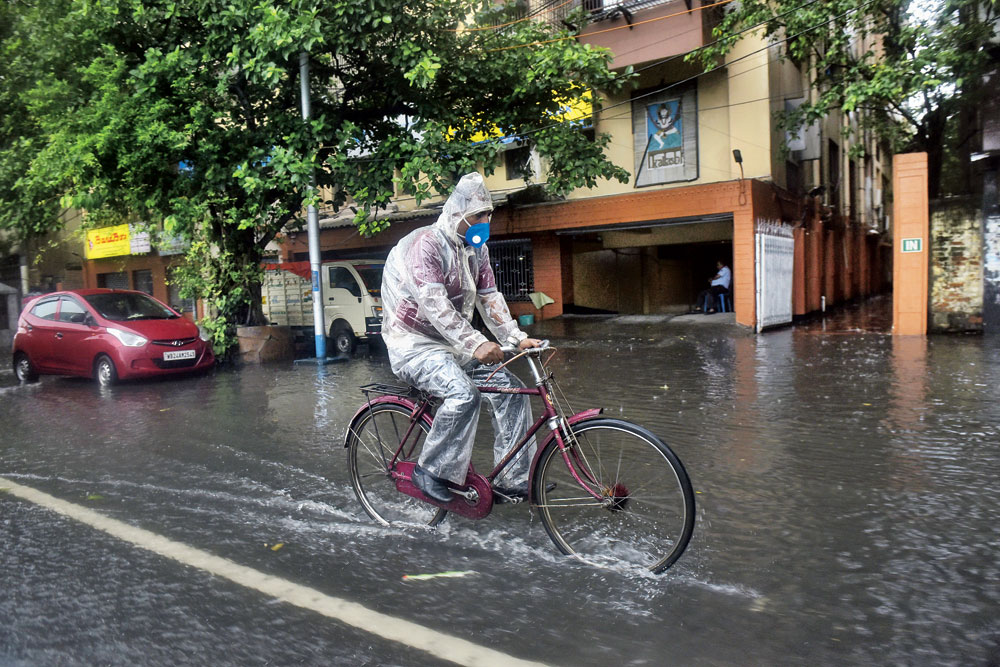 A man cycles through Chowringhee in the rain on Friday morning.