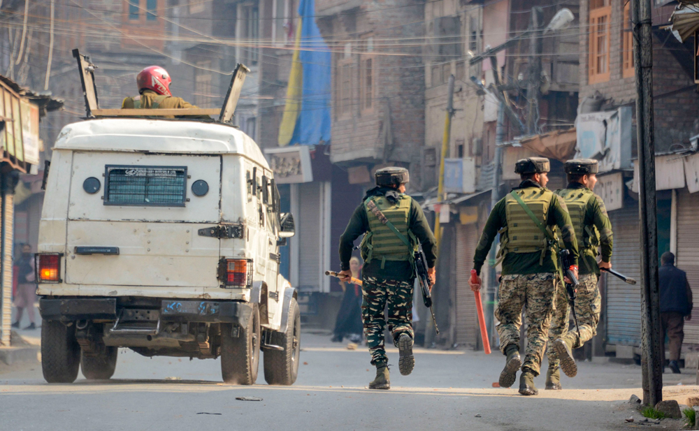 Security personnel chase away stone-pelting youth in Srinagar on Tuesday