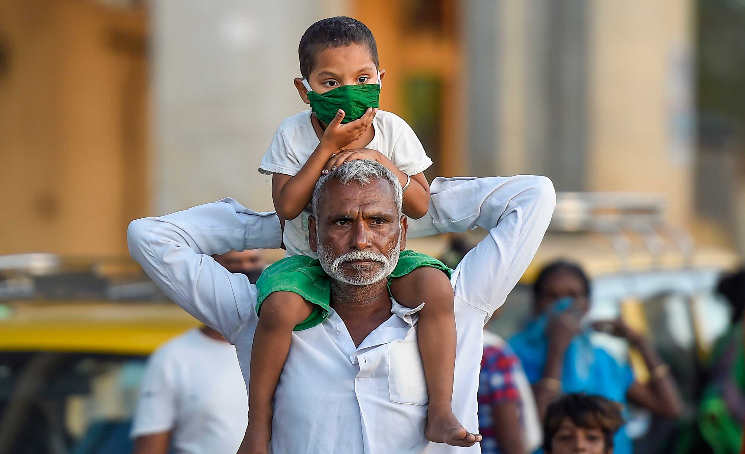 A child wearing a face mask sits on the shoulders of a relative during the nationwide lockdown at Sion in Mumbai on Wednesday.