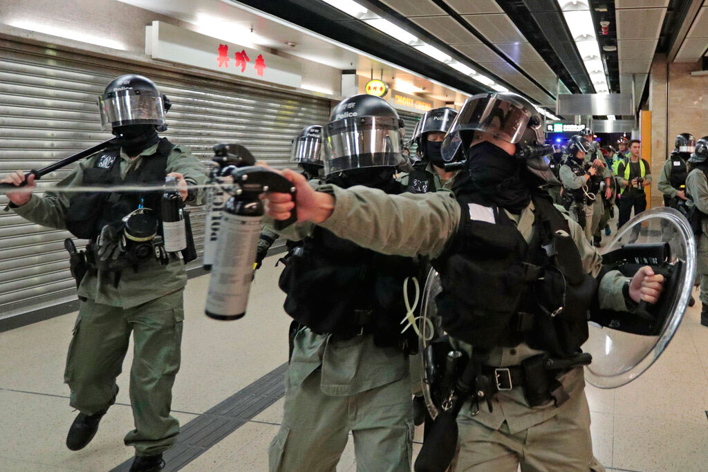 A riot police fires pepper spray at people at a shopping mall in Hong Kong on November 3, 2019.