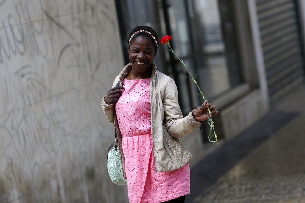 A young woman smiles while carrying a red carnation, symbol of the April 25th Portuguese revolution, in Lisbon's Mouraria neighborhood, Saturday, April 25, 2020. Portugal marks Saturday the anniversary of the 1974 revolution that restored democracy in the country, however due to the coronavirus outbreak this year without the celebrations that usually attract hundreds of thousands.