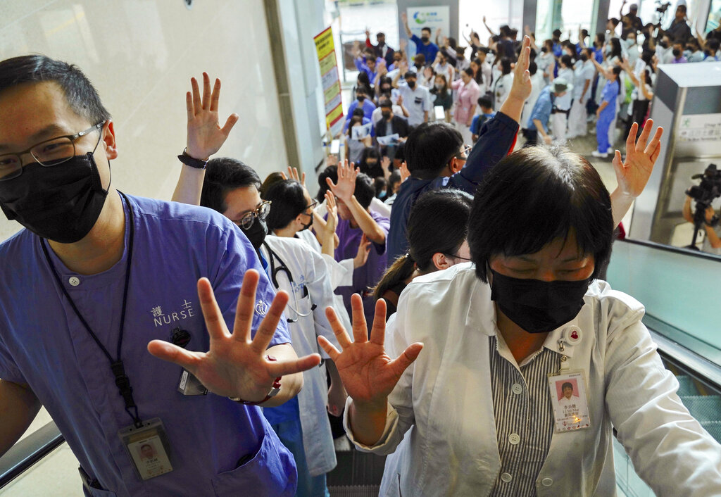 Medical workers display their palm with five fingers, signifying the five demands of protesters and chanted slogans as they stood in the foyer of the hospital before moving to different floors of the building at the Prince of Wales Hospital in Hong Kong on Monday, September 16, 2019