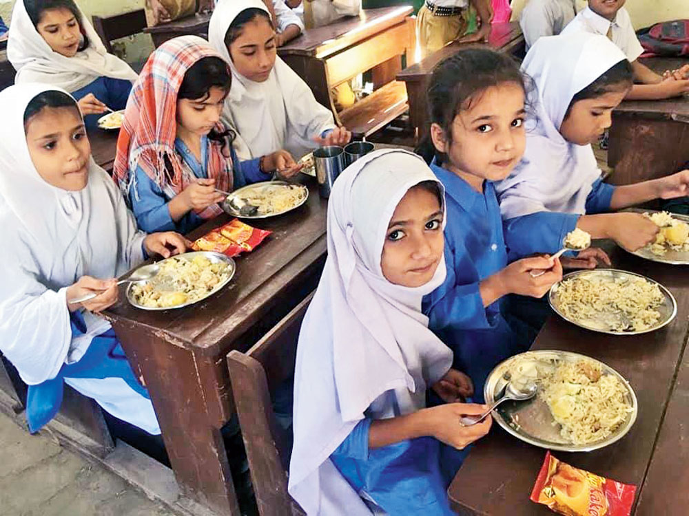 School children in Pakistan's Qayyumabad eating meals made possible by the organisation