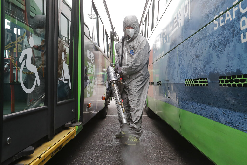 A worker wearing a protective suit sprays disinfectant as a precaution against the coronavirus at a bus garage in Seoul, South Korea