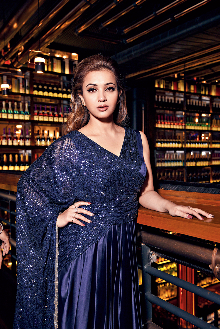 "This dark blue satin sari-gown is perfect for a cocktail do, with a dreamy and romantic glam look. The gown is pleated around the waist. The sequinned pallu with silver tassels made out of pipes and beads lend a touch of shimmer and shine to the outfit. ""This new-age sari is perfect for those who want to ace a luxe, chic and trendy look. The illumination of the pallu and the satin draped blouse is arranged to attain the perfect balance of form,"" said Jyotee. ""This gown is also a great option for a night party, it is so glamorous!"" said Koushani."