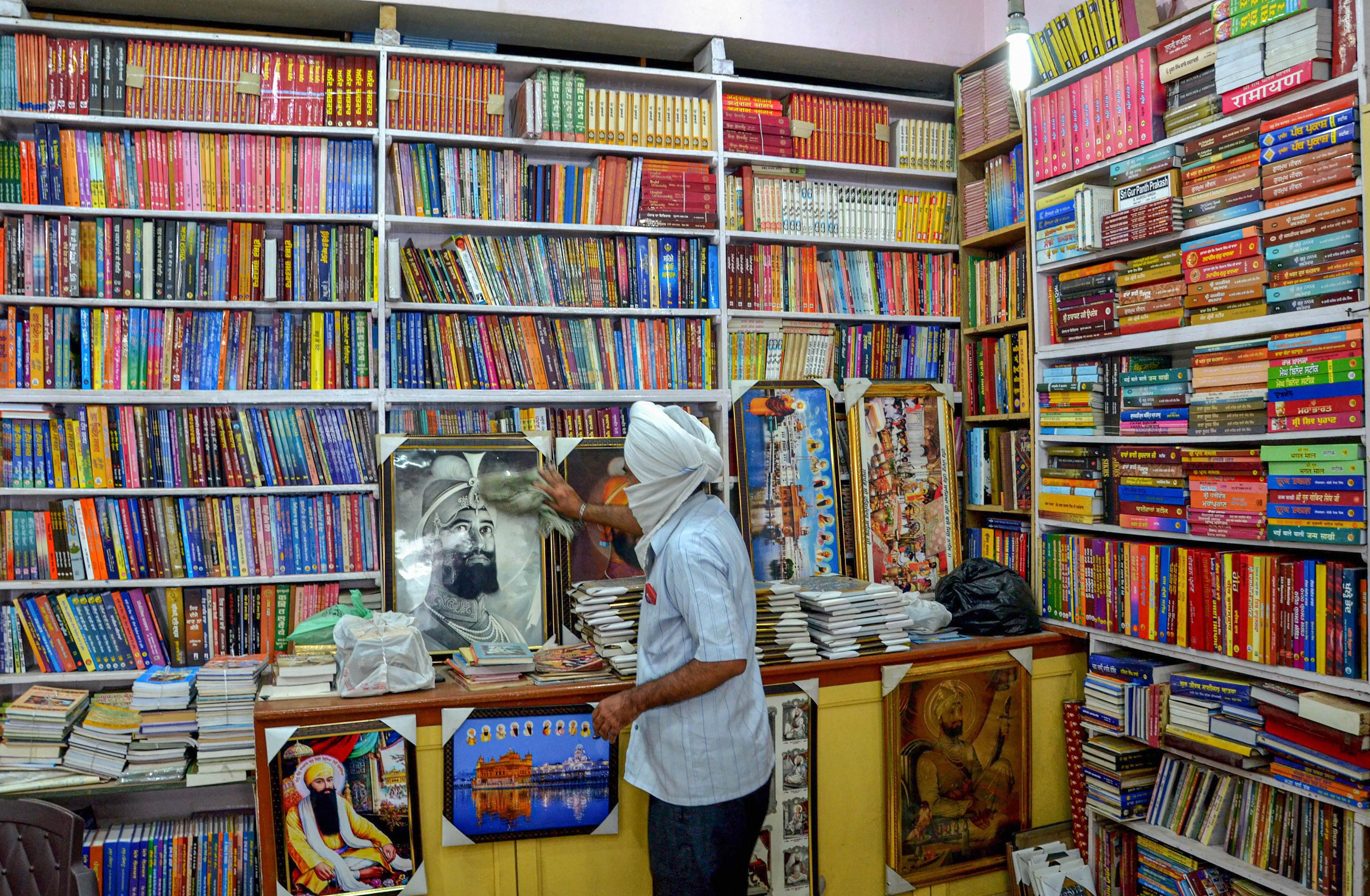 A shopkeeper cleans a portrait inside his book store near Golden Temple after authorities eased restrictions, during the ongoing COVID-19 nationwide lockdown, in Amritsar, Tuesday, June 2, 2020.
