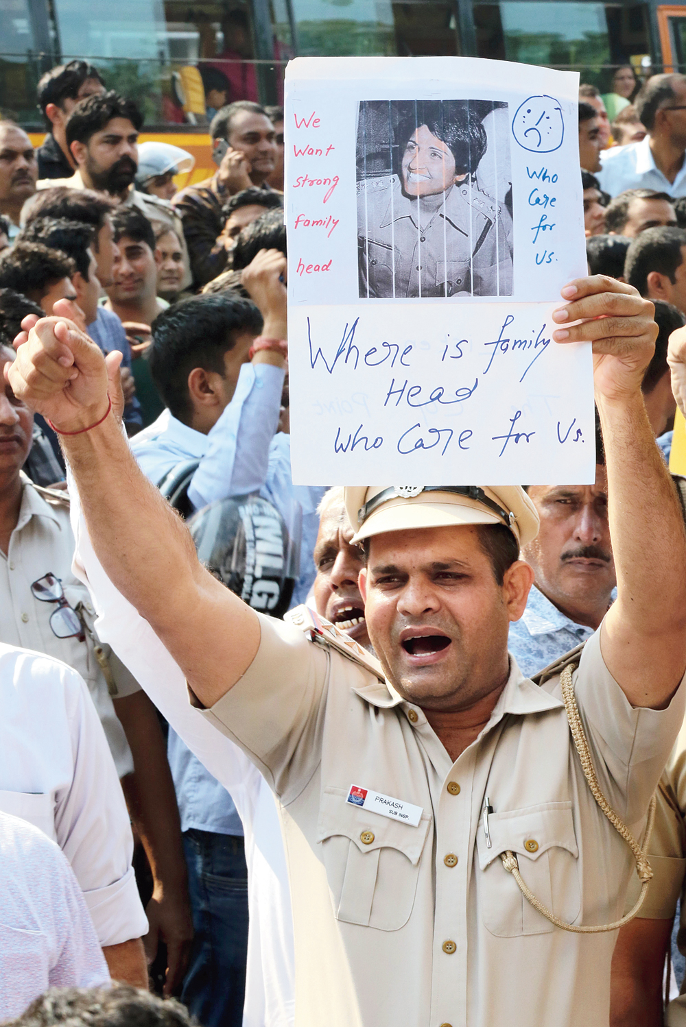 """A policeman holds up a poster featuring Kiran Bedi. A line in the poster reads: """"We want strong family head."""""""