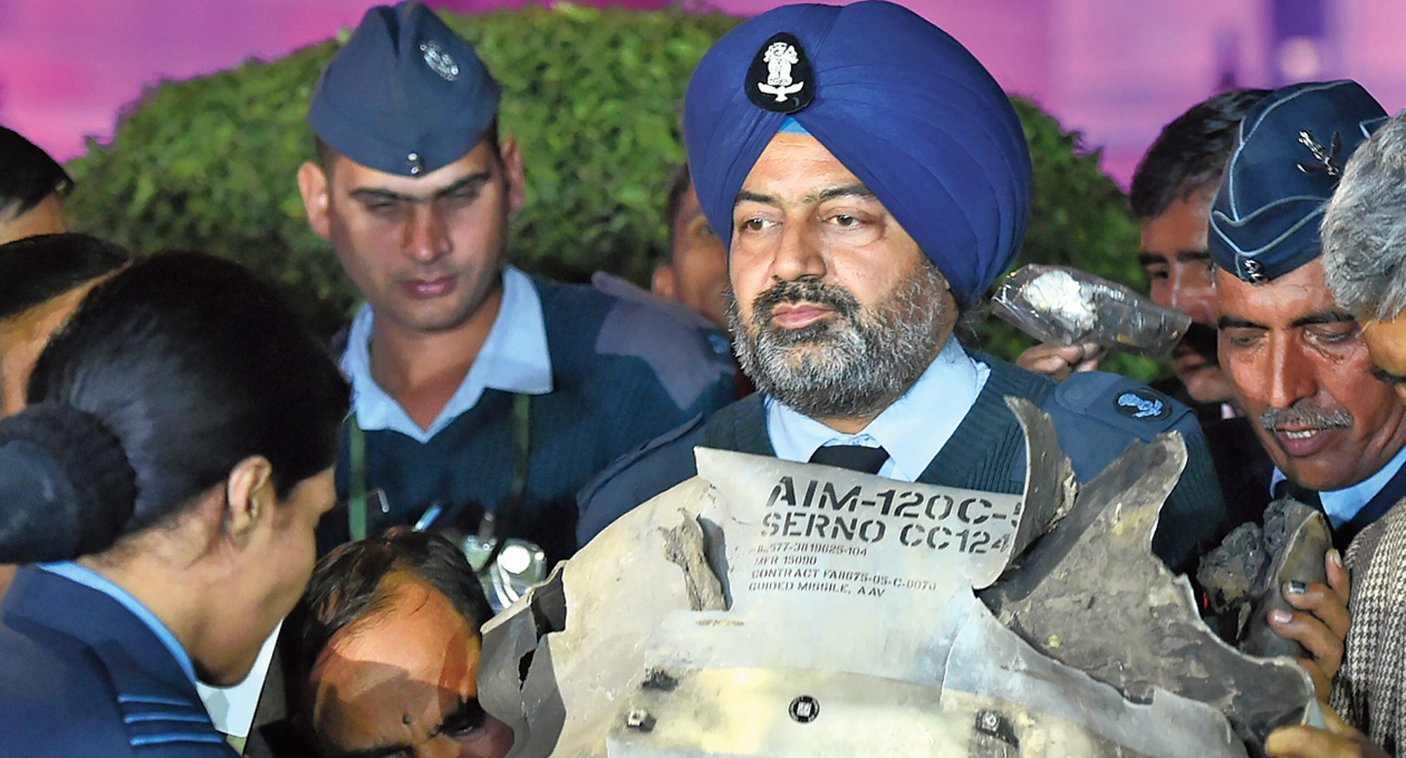 An IAF officer shows a section of an exploded AMRAAM missile at the news conference in Delhi on Thursday.