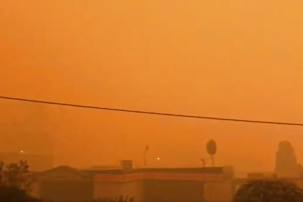 In this Tuesday, December 31, 2019, image from video, smoke from wildfires covers Batehaven, near Batemans Bay, New South Wales, Australia