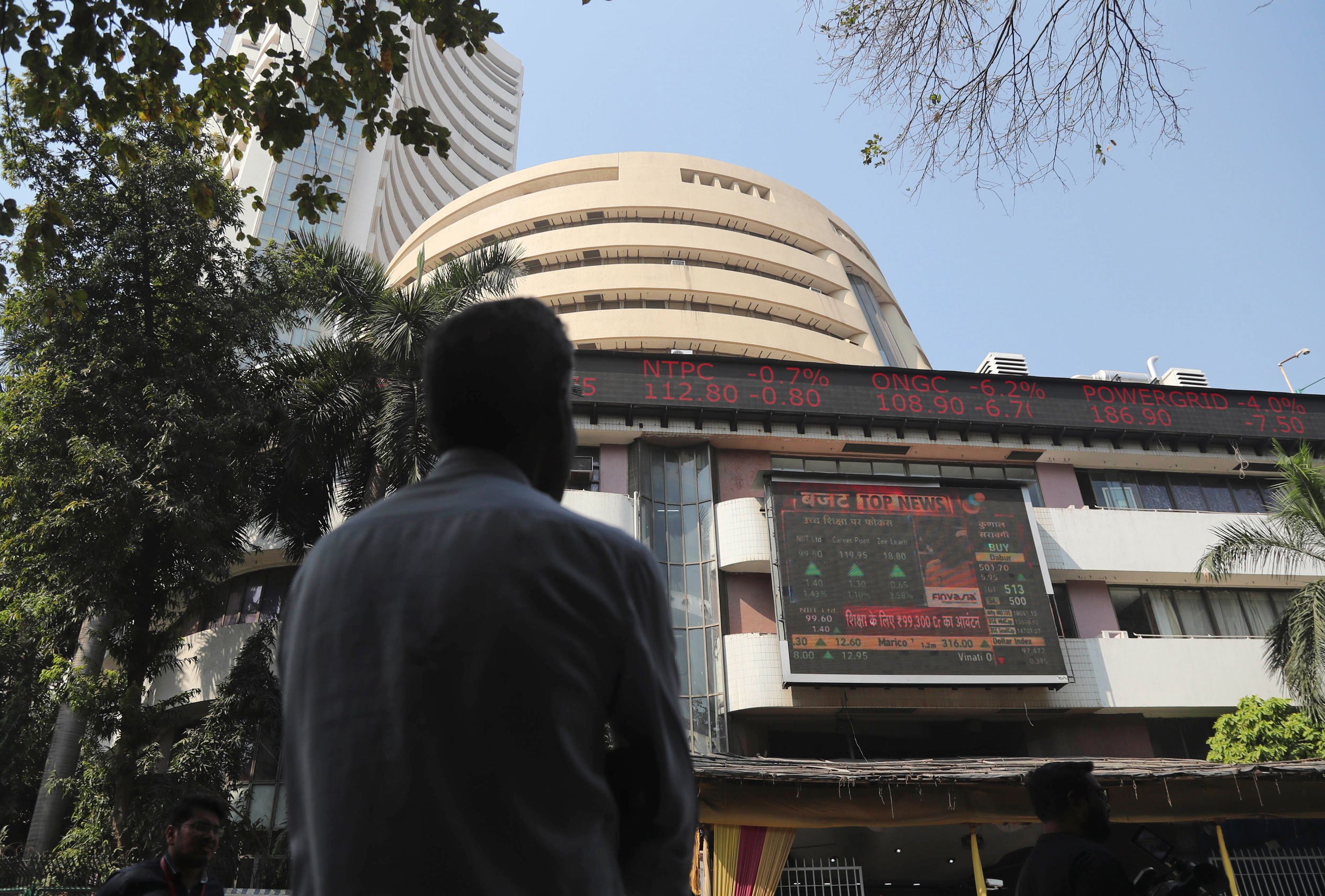 A man watches the stock exchange index on a display screen on the facade of the the BSE building in Mumbai.