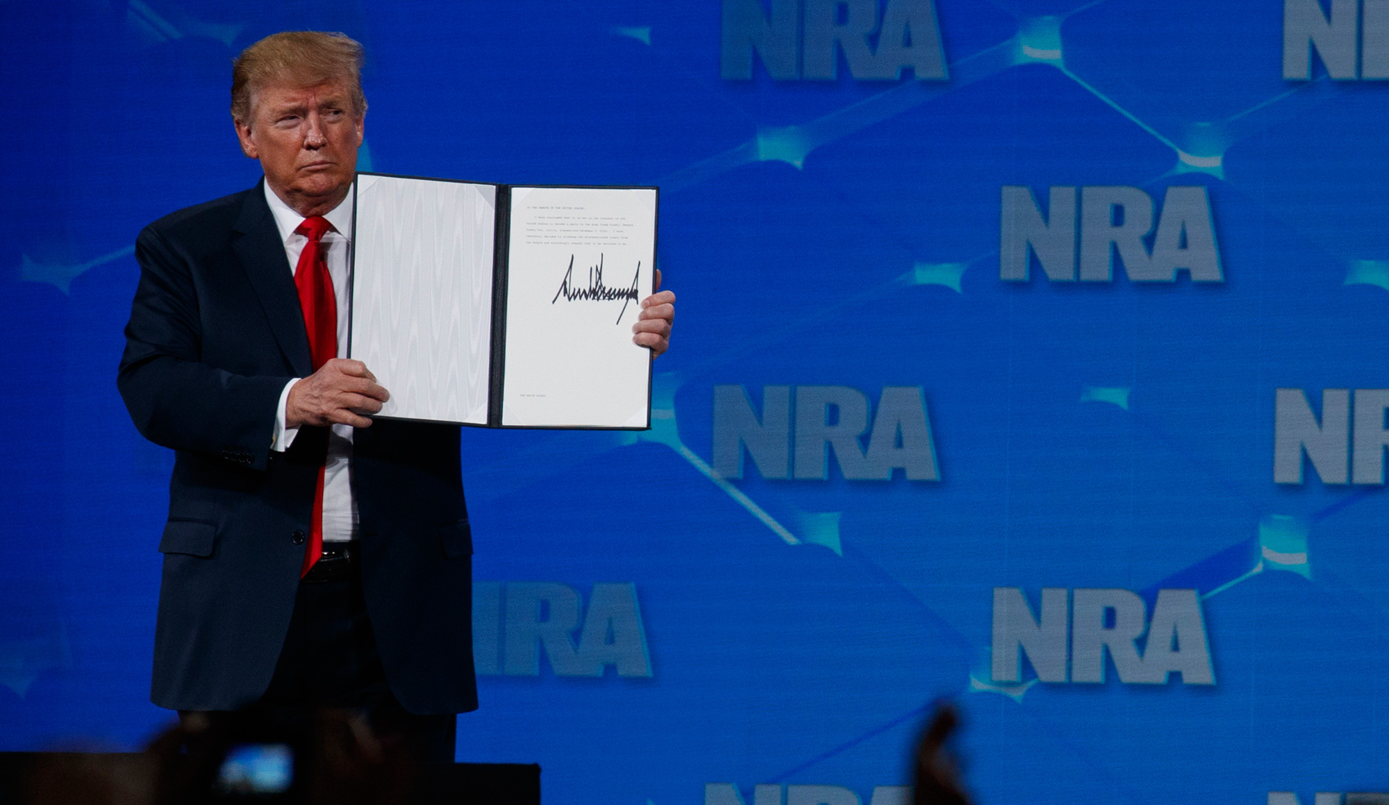 President Donald Trump holds up a letter to the Senate about the UN Arms Trade Treaty as he speaks to the annual meeting of the National Rifle Association on Friday, April 26, 2019, in Indianapolis.