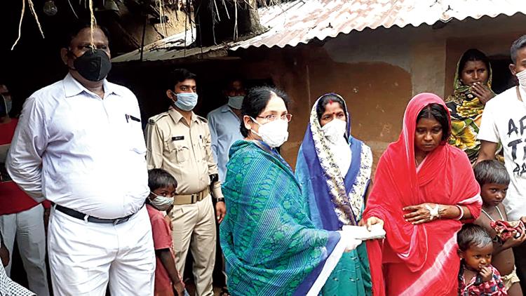 JMM's Ichagarh MLA Sabita Mahto hands over money to deceased Hazari Pramanik's wife at Chhatardih village in Seraikela-Kharsawan district on Wednesday.