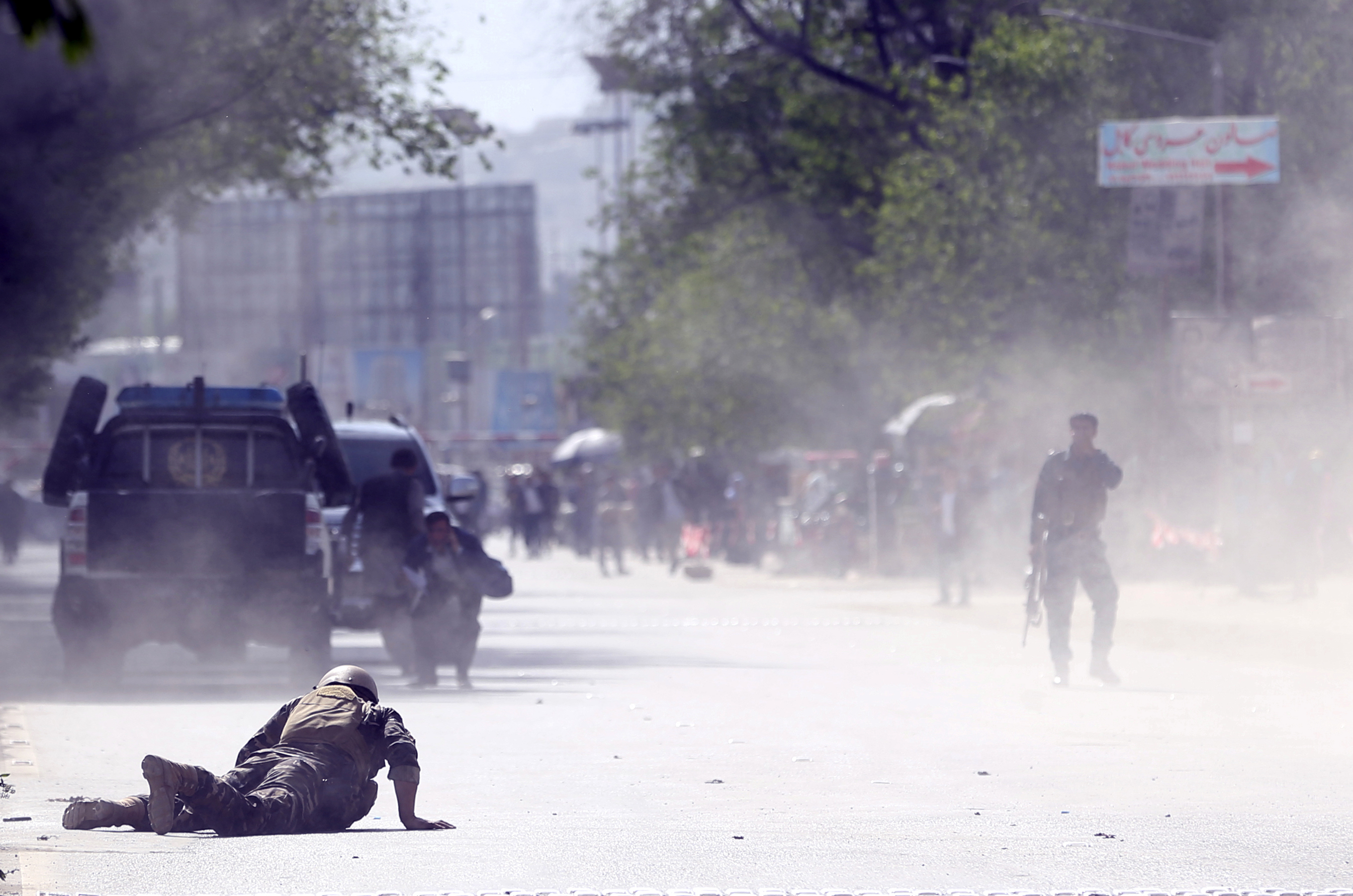 A soldier and a civilian lie low at the site of a suicide attack after the second bombing in Kabul on April 30, 2018