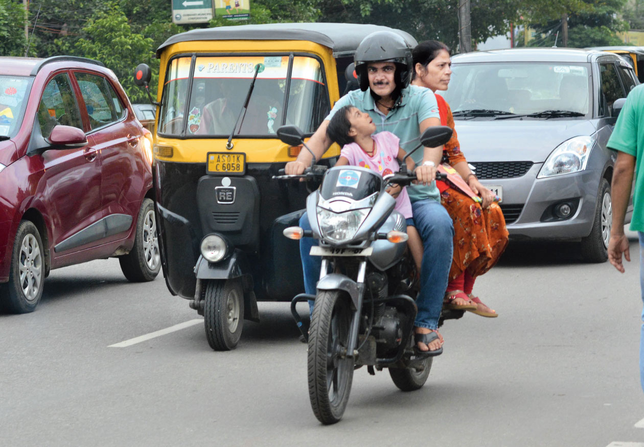 A child rides pillion on a bike.