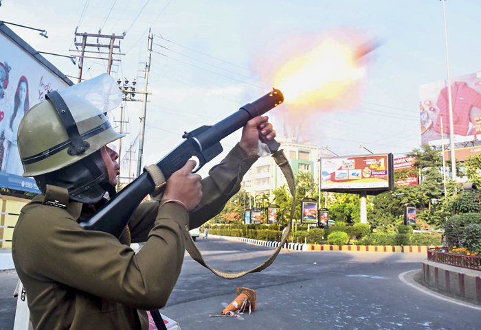 A policeman fires a teargas shell to disperse anti-bill protesters in Guwahati on Thursday