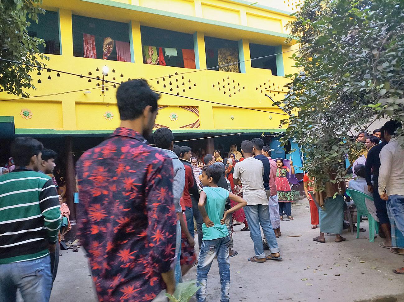 Neighbours gather in front of Masudul Rahaman's house at Nakashipara.