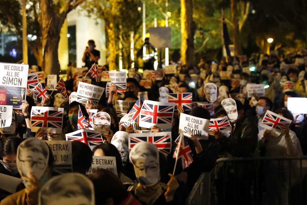 Protesters wear masks of Simon Cheng, a Hong Kong British Consulate employee who was detained in China, as they gather for a rally outside of the British Consulate in Hong Kong, Friday, Nov. 29, 2019.